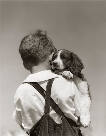simsearch:846-02793283,k - 1930s - 1940s BACK VIEW OF BOY IN CORDUROY OVERALLS HOLDING SPRINGER SPANIEL PUPPY Stock Photo - Rights-Managed, Code: 846-05646259