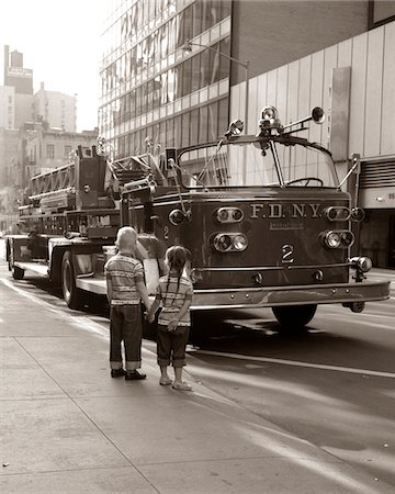 1970s 2 CHILDREN BOY GIRL HOLDING HANDS LOOKING AT FIRE TRUCK PARKED ON STREET NEW YORK CITY Stock Photo - Rights-Managed, Code: 846-05646324