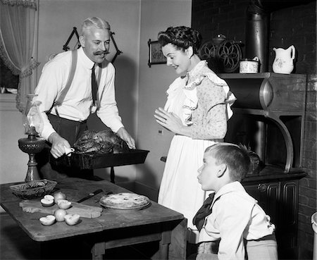 simsearch:846-02793283,k - 1890s - 1900s MOCK TURN OF THE 20TH CENTURY THANKSGIVING DINNER FATHER TAKING TURKEY OUT OF WOOD-BURNING STOVE SHOWING IT TO WIFE AND SON Stock Photo - Rights-Managed, Code: 846-05646329