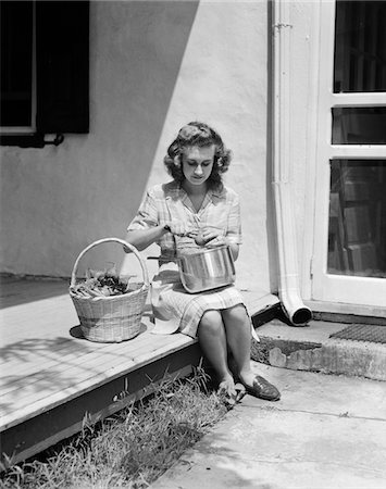 1940s WOMAN WEARING PLAID DRESS AND APRON SITTING ON PORCH OF FARMHOUSE WITH BASKET OF VEGETABLES PEELING TOMATO OVER POT Stock Photo - Rights-Managed, Code: 846-05646357