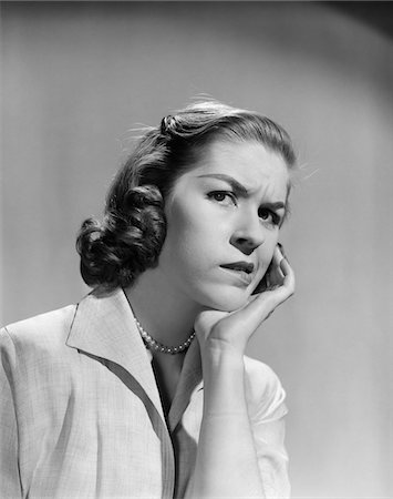 1950s - 1960s WOMAN PORTRAIT WORRIED FACIAL EXPRESSION HAND TO CHEEK TOOTH PAIN Stock Photo - Rights-Managed, Code: 846-05646395