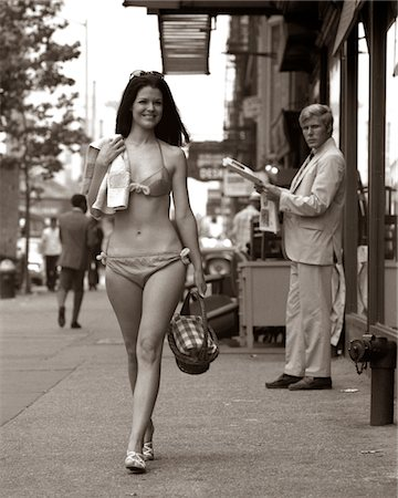 1970s MAN OGLING SEXY SMILING YOUNG WOMAN WALKING DOWN CITY STREET WEARING ONLY A BIKINI BATHING SUIT Stock Photo - Rights-Managed, Code: 846-05646429