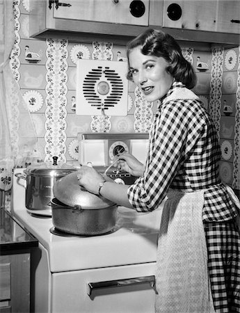 1950s HOUSEWIFE WEARING CHECKERED DRESS STANDING IN KITCHEN STIRRING POT ON STOVE LOOKING OVER SHOULDER Stock Photo - Rights-Managed, Code: 846-05646438