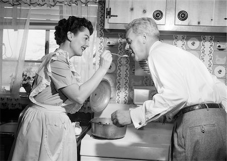simsearch:846-02793283,k - 1950s HOUSEWIFE IN KITCHEN HAVING HUSBAND TASTE FOOD ON STOVE Stock Photo - Rights-Managed, Code: 846-05646444