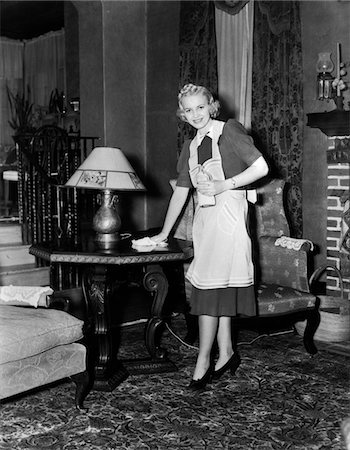 1940s BLONDE WOMAN HOUSEWIFE MAID WEARING APRON CLEANING POLISHING WOODEN END TABLE IN ORNATE LIVING ROOM Stock Photo - Rights-Managed, Code: 846-05646454