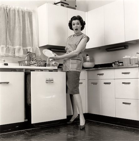 1950s WOMAN HOUSEWIFE WEARING SMOCK PUTTING DISHES IN AUTOMATIC DISHWASHER IN SUBURBAN KITCHEN Stock Photo - Rights-Managed, Code: 846-05646464