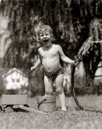 1940s - 1950s WET YOUNG BOY TODDLER OUTSIDE PLAYING WITH WATER HOSE Stock Photo - Rights-Managed, Code: 846-05646476