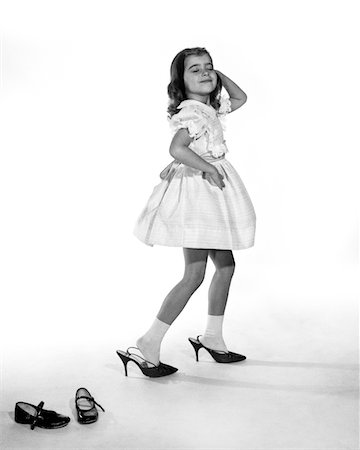 foot model - 1960s GIRL MAKING GLAMOUR POSE HAVING STEPPED OUT OF HER SHOES INTO HER MOTHERS ADULT HIGH HEELS Stock Photo - Rights-Managed, Code: 846-05646482