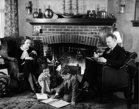 1930s FAMILY OF FOUR SITTING IN FRONT FIREPLACE MOTHER KNITTING FATHER READING SMOKING PIPE KIDS DOING HOMEWORK Stock Photo - Rights-Managed, Code: 846-05646502