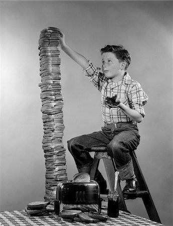 1950s BOY EATING JELLY TOAST SITTING ON LADDER STACKING UP TALL PILE OF TOAST FROM TOASTER Stock Photo - Rights-Managed, Code: 846-05646539