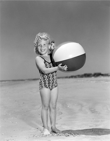 1950s SMILING GIRL STANDING ON BEACH HOLDING BEACH BALL LOOKING AT CAMERA Stock Photo - Rights-Managed, Code: 846-05646533