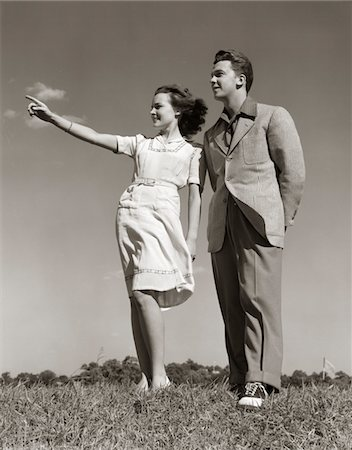 1940s TEENAGE COUPLE STANDING TOGETHER OUTDOORS GIRL POINTING Stock Photo - Rights-Managed, Code: 846-05646559