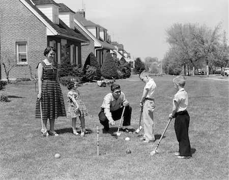 1950s FAMILY MOTHER FATHER 3 CHILDREN PLAYING CROQUET FRONT LAWN SUBURBAN HOME Stock Photo - Rights-Managed, Code: 846-05646571