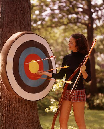 1970s WOMAN FEMALE ARCHER PULLING ARROWS FROM ARCHERY TARGET Stock Photo - Rights-Managed, Code: 846-05646597