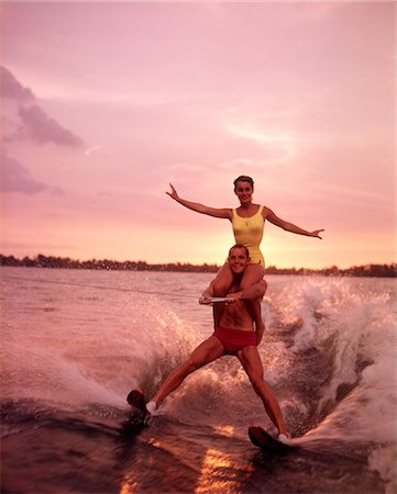 1960s COUPLE WATER SKIING WOMAN YELLOW BATHING SUIT RIDING ON THE SHOULDERS  OF MAN RED TRUNKS AT SUNSET Stock Photo - Rights-Managed, Code: 846-05646630
