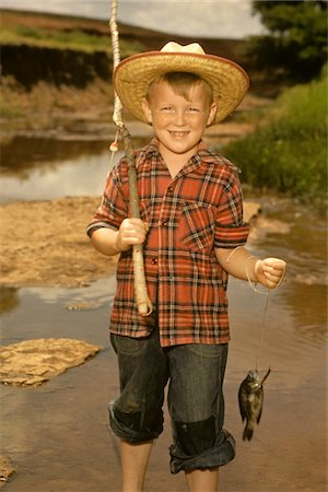 1950s SMILING BOY STRAW HAT HOLDING FISHING POLE WEARING PLAID SHIRT BLUE JEANS Stock Photo - Rights-Managed, Code: 846-05646631