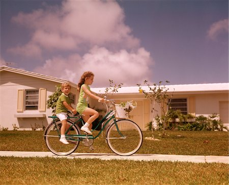 1970s GIRL RIDING BIKE ON SUBURBAN STREET BOY RIDES PIGGY BACK Stock Photo - Rights-Managed, Code: 846-05646719