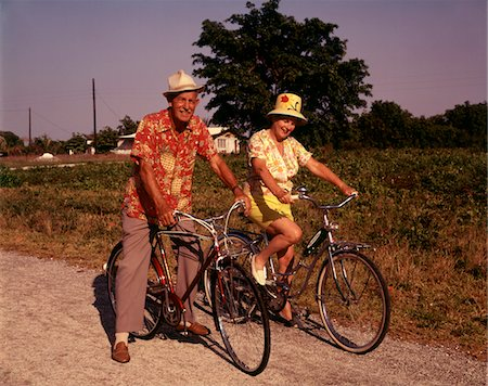 1970s SENIOR ELDERLY RETIRED COUPLE RIDING BIKES WEARING STRAW HATS HAWAIIAN PRINT SHIRTS Stock Photo - Rights-Managed, Code: 846-05646711