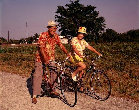 1970s SENIOR ELDERLY RETIRED COUPLE RIDING BIKES WEARING STRAW HATS HAWAIIAN PRINT SHIRTS Stock Photo - Rights-Managed, Code: 846-05646711