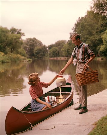 1960s YOUNG COUPLE LOADING PICNIC BASKET THERMOS INTO CANOE Stock Photo - Rights-Managed, Code: 846-05646750