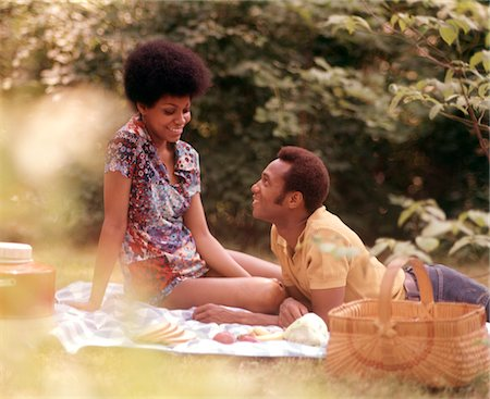 1970s ROMANTIC AFRICAN-AMERICAN COUPLE MAN WOMAN PICNIC BASKET SITTING GRASS Stock Photo - Rights-Managed, Code: 846-05646774