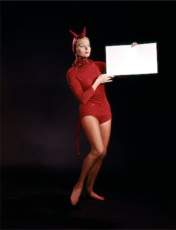 1960s BLOND YOUNG WOMAN IN RED DEVIL COSTUME HOLDING SIGN BOARD IN HANDS Stock Photo - Rights-Managed, Code: 846-05646956