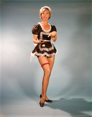 1960s WOMAN SMILING WEARING SHORT BLACK & WHITE LACE FRENCH MAID COSTUME POINTING TO SILVER TRAY Stock Photo - Rights-Managed, Code: 846-05646952