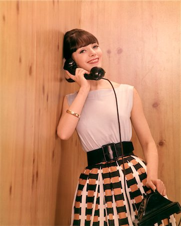 1950s - 1960s SMILING BRUNETTE WOMAN  TALKING TELEPHONE LEANING AGAINST WOOD PANEL WALL Stock Photo - Rights-Managed, Code: 846-05646953