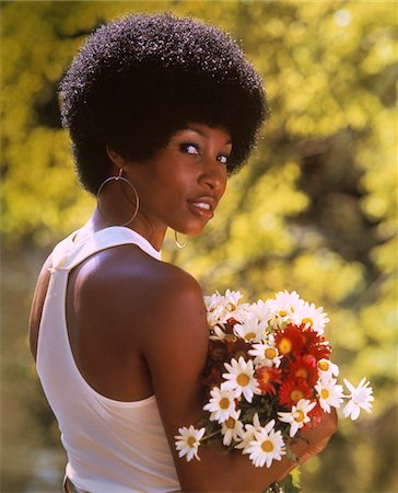 1970s SMILING AFRICAN-AMERICAN WOMAN WEARING HOOP EARRINGS WHITE TANK TOP HOLDING A BOUQUET SPRING FLOWERS Stock Photo - Rights-Managed, Code: 846-05646991