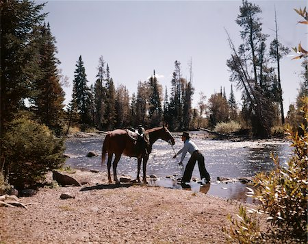 1970s COWBOY STANDING IN STREAM LEADING HORSE BY REINS TO WATER Stock Photo - Rights-Managed, Code: 846-05647017