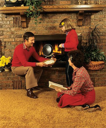 sweater and fireplace - 1970s - 1980s FAMILY FATHER MOTHER DAUGHTER SITTING BY FIREPLACE POPPING CORN Stock Photo - Rights-Managed, Code: 846-05647085