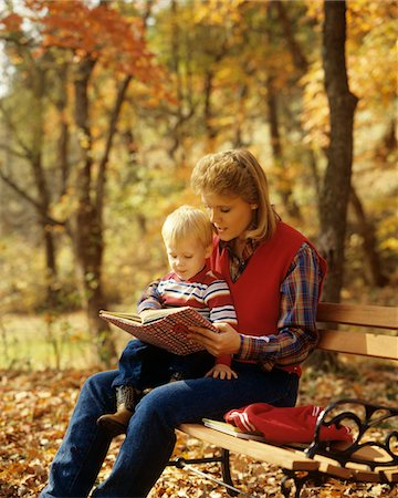 1980s WOMAN READING BOOK TO TODDLER SITTING AUTUMN PARK BENCH Stock Photo - Rights-Managed, Code: 846-05647087