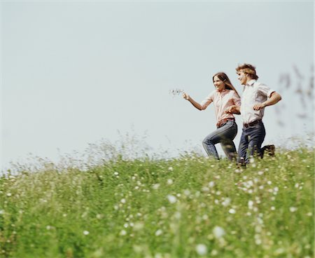 1970s  YOUNG TEEN COUPLE BOY GIRL RUNNING FIELD  WILDFLOWERS Stock Photo - Rights-Managed, Code: 846-05647148