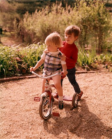 1960s - 1970s YOUNG BOY AND GIRL PLAYING TOGETHER RIDING TRICYCLE Stock Photo - Rights-Managed, Code: 846-05647143