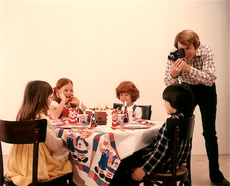 1970s FATHER WITH HOME MOVIE CAMERA TAKING PICTURES BIRTHDAY PARTY CHILDREN AT TABLE Stock Photo - Rights-Managed, Code: 846-05647164