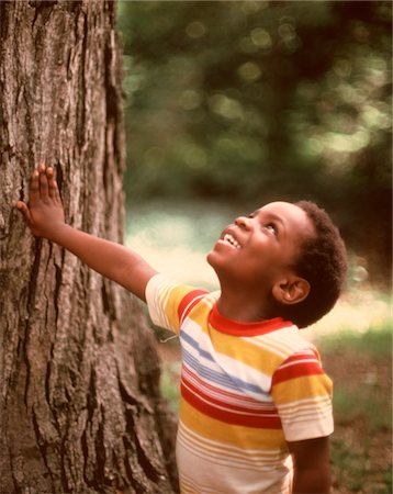 1970s SMILING AFRICAN-AMERICAN BOY LOOKING UP TREE TRUNK WEARING  STRIPED TEE SHIRT Stock Photo - Rights-Managed, Code: 846-05647161