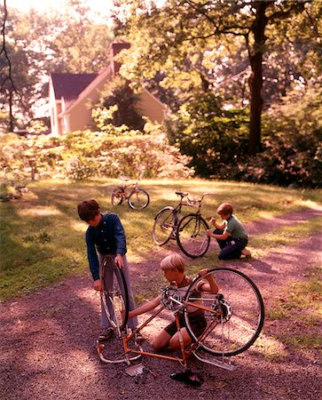1970s 3 BOYS BACKYARD DRIVEWAY SUBURBAN HOUSE WORK ON BICYCLE MAINTENANCE REPAIR Stock Photo - Rights-Managed, Code: 846-05647162