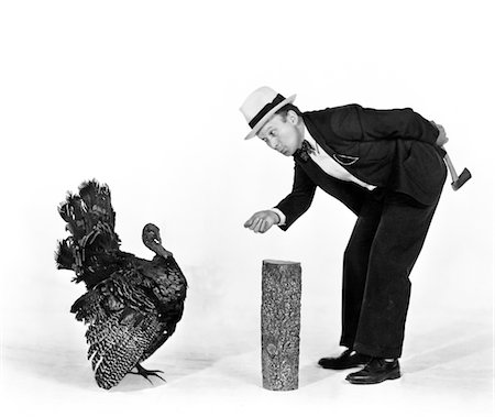 1930s - 1940s MAN CHARACTER WITH HATCHET TRYING TO CATCH A THANKSGIVING TURKEY Stock Photo - Rights-Managed, Code: 846-05647179