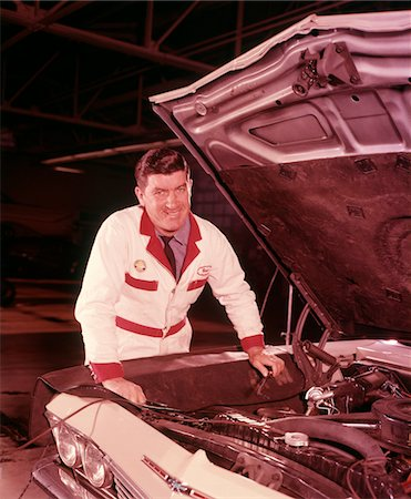 1960s MAN SMILING AUTOMOBILE MECHANIC IN WHITE OVERALLS WORKING HOOD UP ON CAR ENGINE IN GAS SERVICE STATION REPAIR SHOP Stock Photo - Rights-Managed, Code: 846-05647187