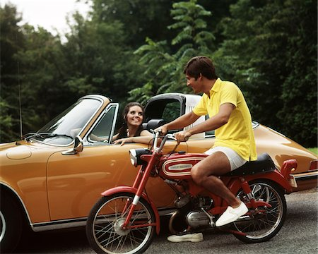 1970s LIFESTYLE TALKING FLIRT COUPLE MAN ON SMALL RED HARLEY DAVIDSON MOTORCYCLE SMILING WOMAN IN ORANGE PORSCHE AUTOMOBILE Stock Photo - Rights-Managed, Code: 846-05647208