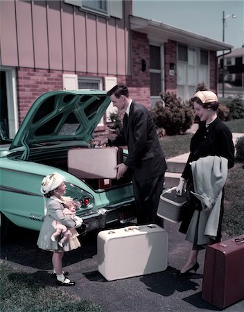 1950s FAMILY MOTHER FATHER DAUGHTER IN FRONT OF SUBURBAN HOUSE PACKING LUGGAGE IN CAR FOR VACATION Stock Photo - Rights-Managed, Code: 846-05647202
