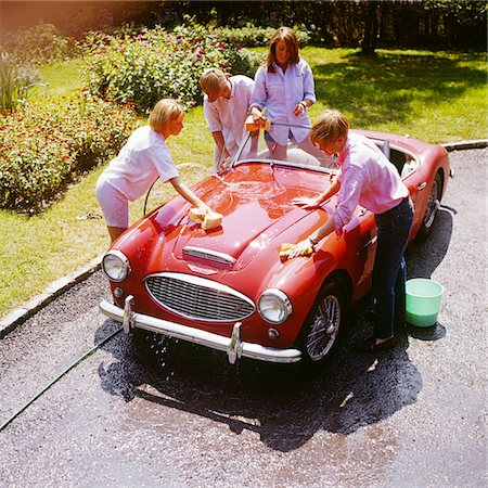 1970s FOUR TEENAGERS WASHING RED AUSTIN HEALEY SPORTS CONVERTIBLE AUTOMOBILE MAN WOMAN OVERHEAD OUTDOOR Stock Photo - Rights-Managed, Code: 846-05647216