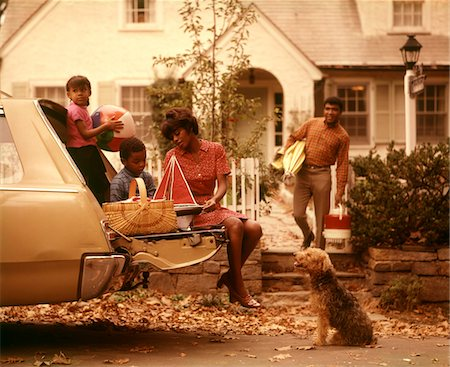 1970s AFRICAN-AMERICAN FAMILY LOADING STATION WAGON PICNIC DOG MOTHER FATHER BOY GIRL SUBURBAN   HOUSE Stock Photo - Rights-Managed, Code: 846-05647227