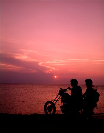 1970s SILHOUETTED COUPLE SUNSET BEACH RIDING CHOPPER MOTORCYCLE BIKE MOTOR CYCLE MOTORCYCLES BIKERS BIKES Stock Photo - Rights-Managed, Code: 846-05647221