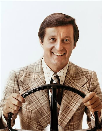 1970s SMILING MAN WEARING LOUD PRINT SHIRT TIE PLAID SPORT JACKET HOLDING STEERING WHEEL DRIVING CAR LOOKING AT CAMERA Stock Photo - Rights-Managed, Code: 846-05647240