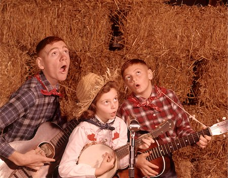preteen boys playing - 1950s - 1960s TWO BROTHERS AND A SISTER PLAYING INSTRUMENTS GUITARS AND BANJO SINGING COUNTRY MUSIC Stock Photo - Rights-Managed, Code: 846-05647251