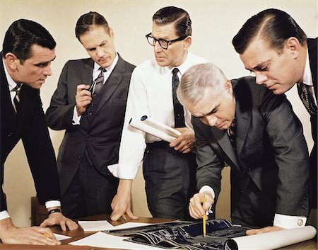 1960s BUSINESSMEN MEETING INSPECTING BLUEPRINTS Not for use with: Beer, Cigars, Cigarettes, Soap, Toothpaste, Mouthwash, Coffee, Tea, or Soft Drinks Stock Photo - Rights-Managed, Code: 846-05647277
