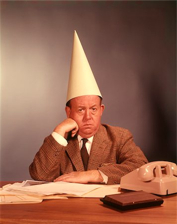 1960s SAD DEPRESSED BUSINESSMAN WEARING DUNCE CAP Stock Photo - Rights-Managed, Code: 846-05647281