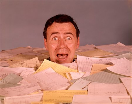 people in panic - 1960s OVERWHELMED SCREAMING BUG-EYED MAN OFFICE WORKER DROWNING IN PAPER WORK UP TO HIS NECK SURROUNDED BY BILLS AND INVOICES Stock Photo - Rights-Managed, Code: 846-05647314