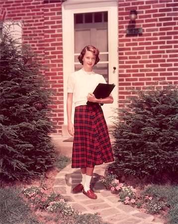 1950s TEENAGE GIRL HIGH SCHOOL STUDENT HOLDING SCHOOL BOOKS WALKING DOWN FLAGSTONE WALK IN FRONT OF BRICK HOUSE Stock Photo - Rights-Managed, Code: 846-05647395